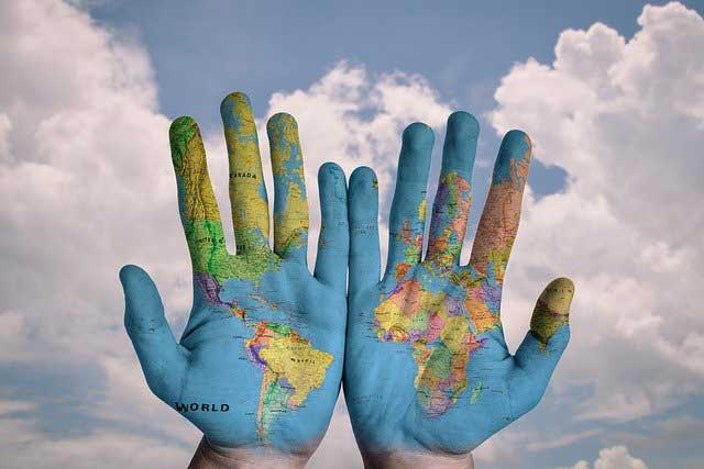 Two hands with the world map painted on them