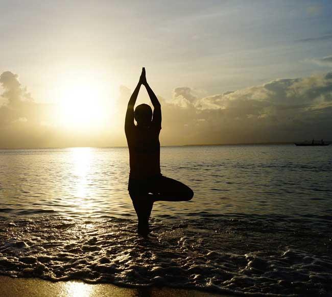 Woman balancing a yoga pose on beach